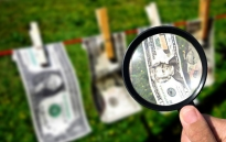 clothes line with money attached and magnifying glass