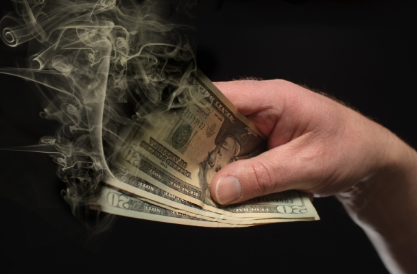 A hand holds money that is burning away.